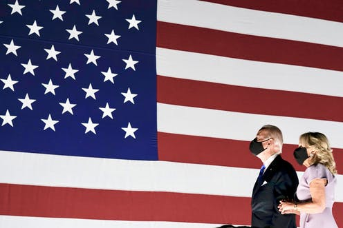 Us presidential nominee Joe Biden and wife Jill stand in front of a US flag