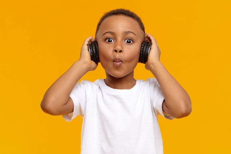 Young boy wearing headphones and whistling.