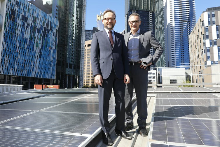 Adam Bandt and Richard Di Natale standing against a Melbourne city skyline.