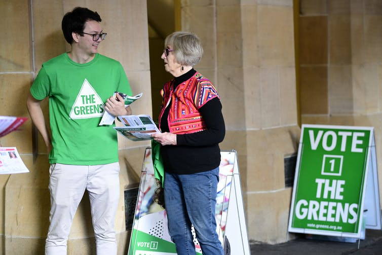 Greens candidate and volunteer, standing next to a Greens placard at a voting booth.
