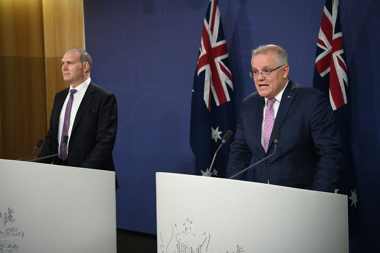 Nev Power and Scott Morrison behind a podium giving a press conference.