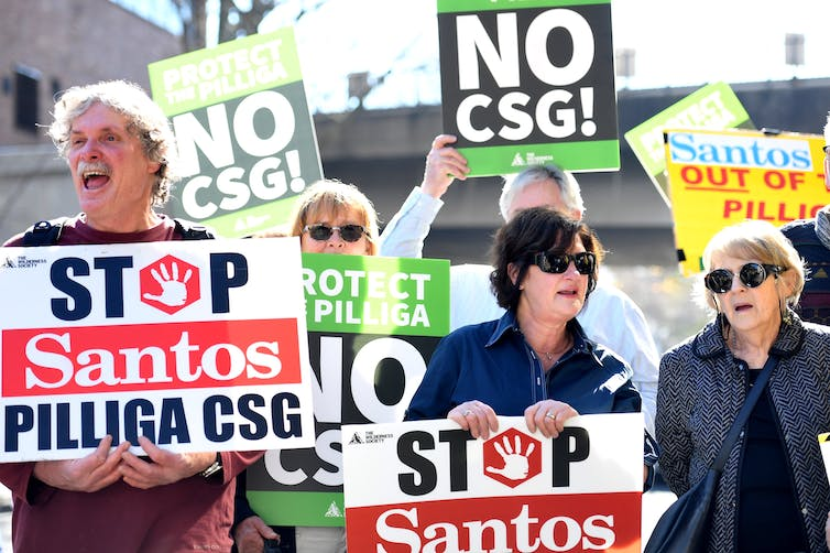 Protesters hold placards against Santos