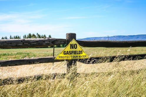 """A yellow triangular sign against a wooden fence reads """"NO GASFIELDS PROTECT OUR WATER"""""""