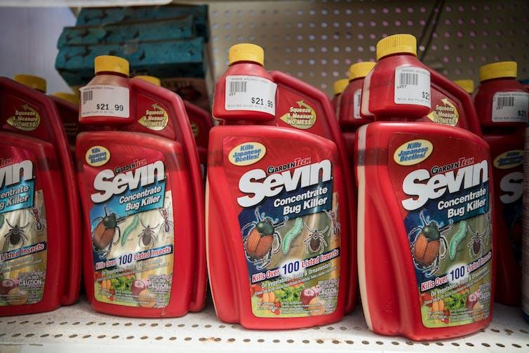 Red bottles of weed killer on store shelf.