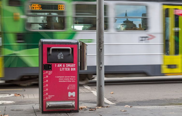 Smart litter bin on pavement with a Melbourne tram passing behind it