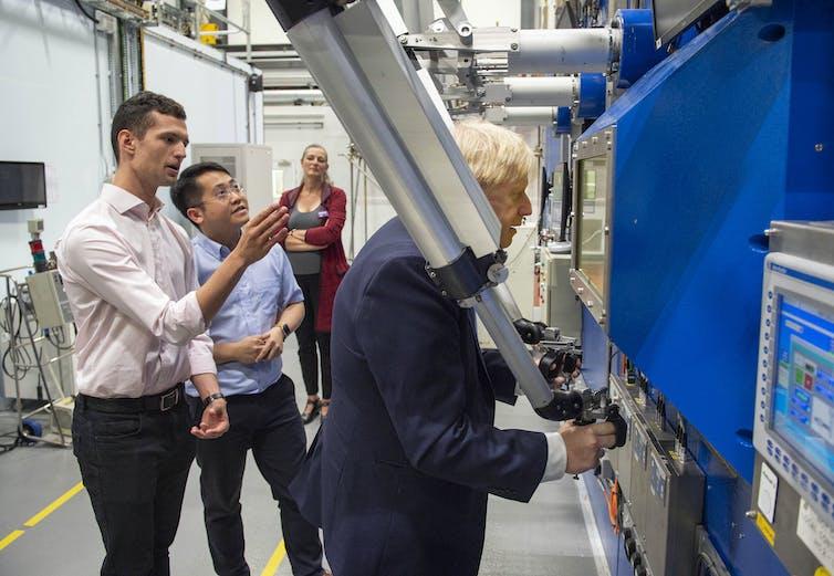 Boris Johnson looks into large industrial machine