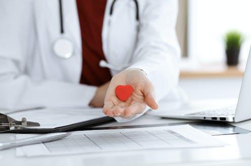 Un médico muestra en su palma la figura de un pequeño corazón