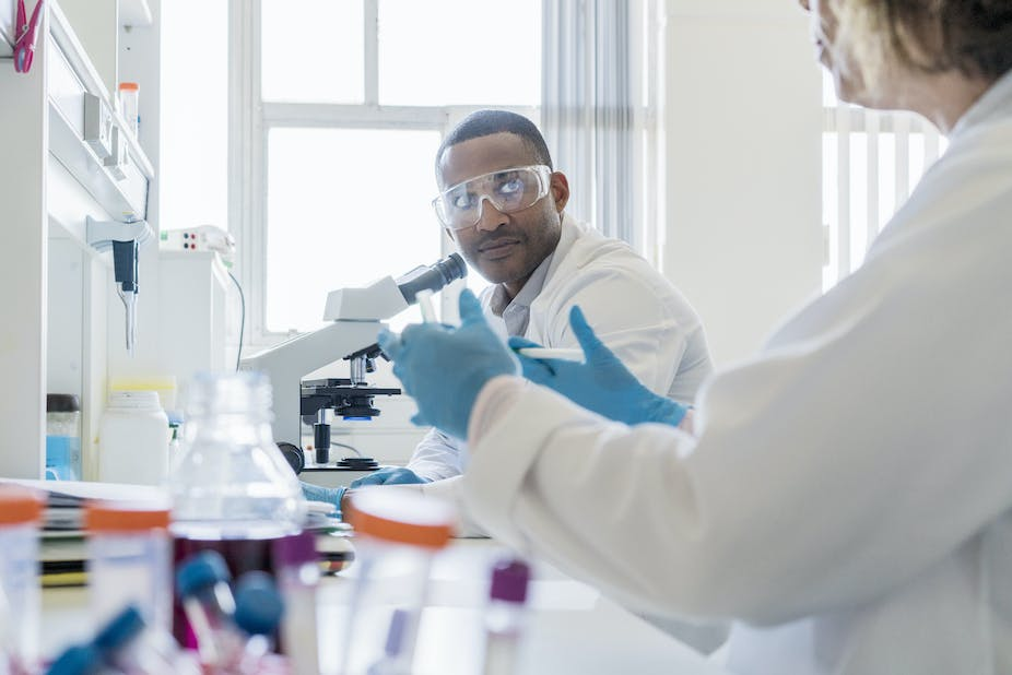 A photo of chemist looking at colleague while working in laboratory.