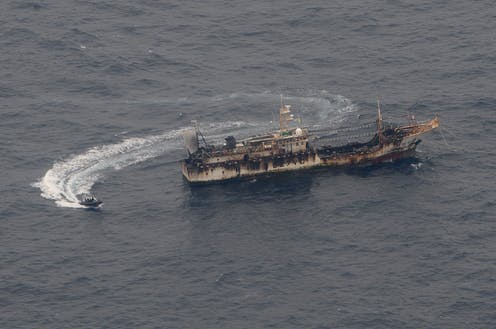 A small ship circles a much larger ship in the ocean