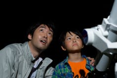 A young boy and his father view the night sky next to a telescope.
