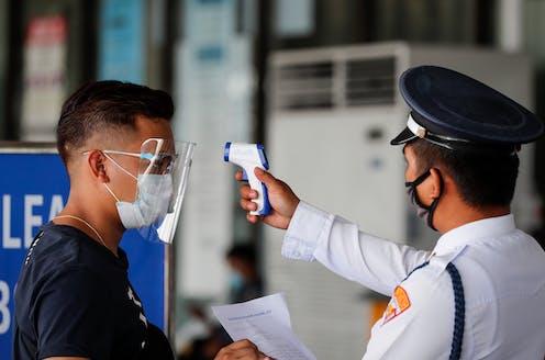Man having his temperature checked at an airport
