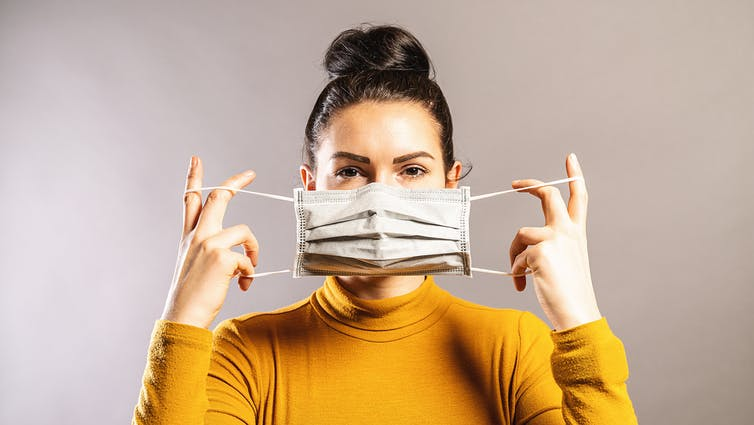 Woman putting a face mask on