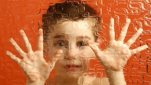 Manos y cara de un niño tras un cristal esmerilado.