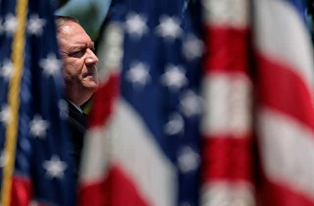 Mike Pompeo surrounded by US flags