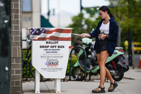 A woman dropping off a ballot in a drop-off box in Denver.