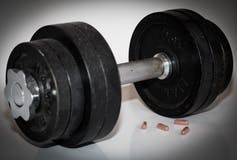 A black dumbbell with drug capsules in the foreground