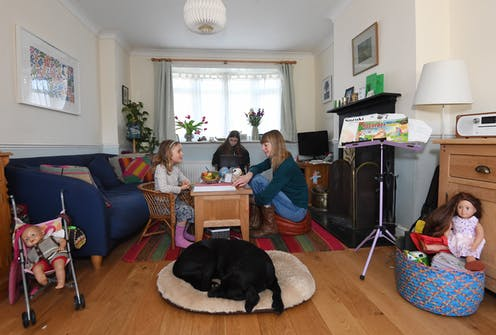 A mother teaches her children at home while a labrador sleeps by the table.