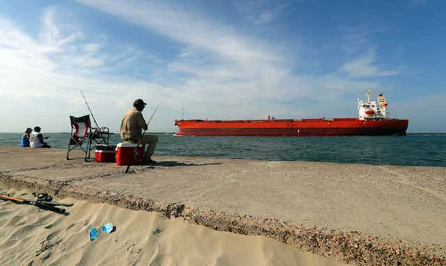 A man sitting on a cooler fishing with a red oil tanker passing by.
