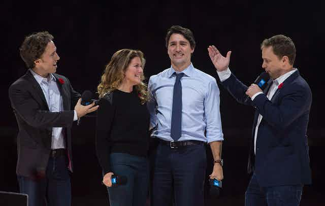 Craig Kielburger stands to the right of Sophie Gregoire-Trudeau and Justin Trudeau on a stage, with his brother Marc to their left.