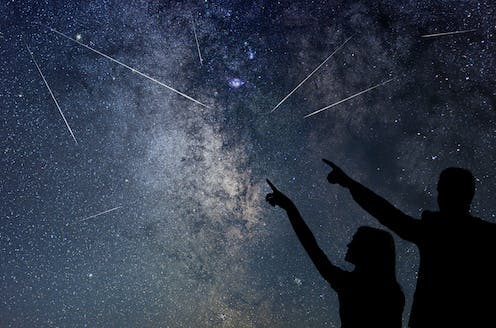 Two people point and look at shooting stars flying through the night sky.