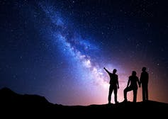 Three people point up to the night sky to look at beautiful constellations.