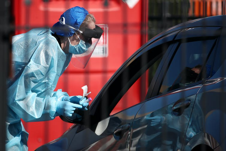Nurse in protective clothing testing car passenger