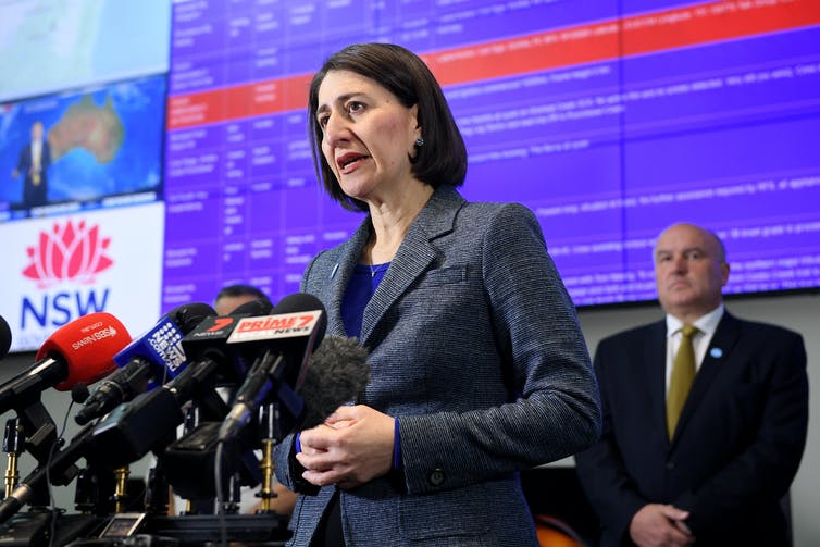 Gladys Berejiklian stands behind a podium at a press conference.