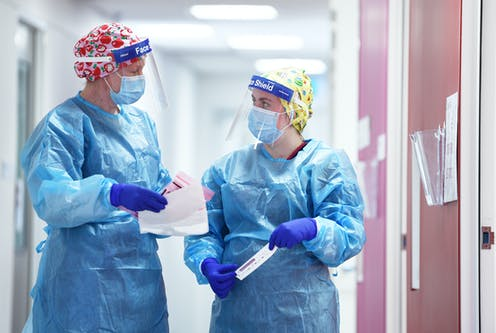 Two nurses wearing personal protective equipment including face shields