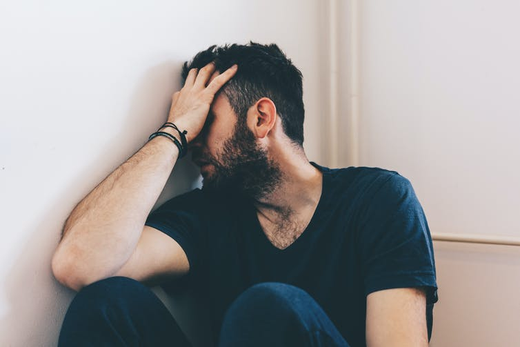 Man sits against the wall with his head in his hand.