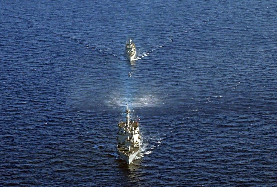 Military ships sail through waters around Crete.