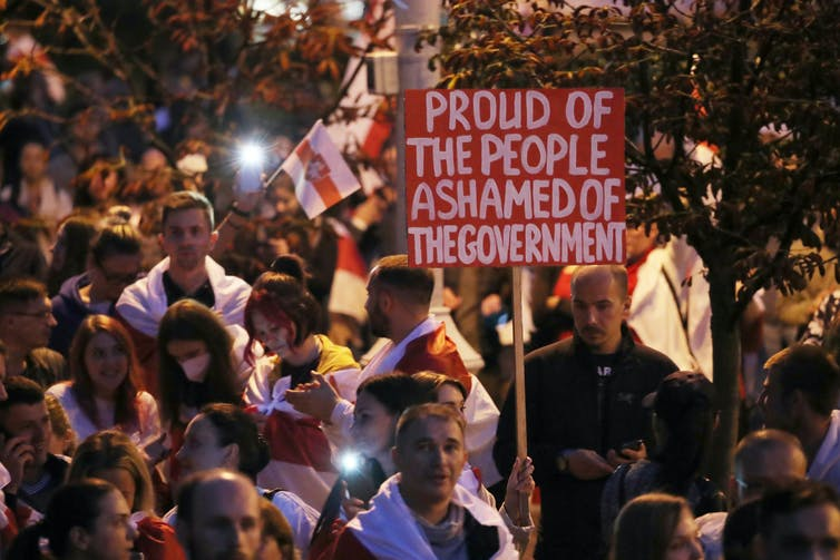 Belarus protestors hold sign saying 'Proud of the people, ashamed of the government'.