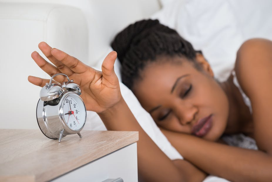 Sleeping woman reaches for alarm clock.