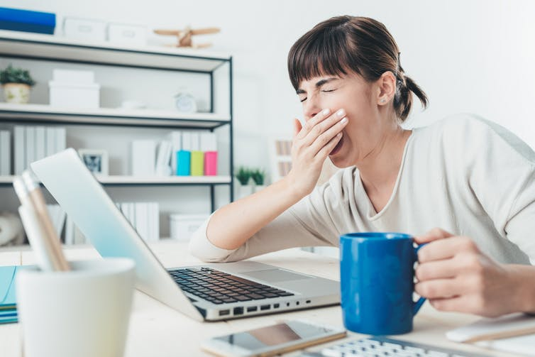 Woman holding cup of coffee yawns in front of her laptop.