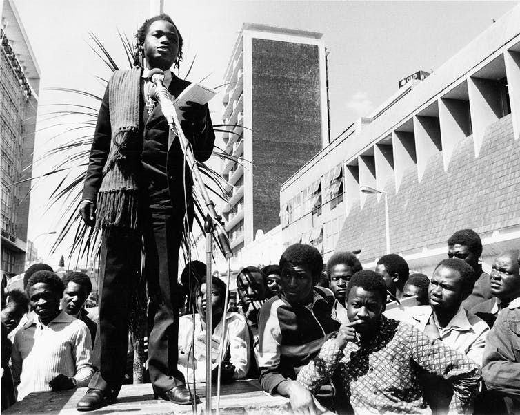 A dreadlocked man stands at a microphone, holding a notebook in an outdoor city space, crowds of people around the platform he stands on.