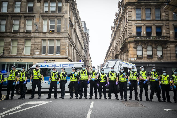 A row of police officers standing in city street.