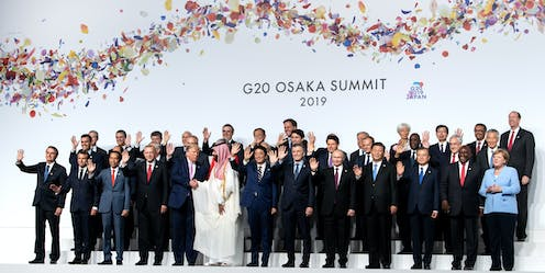 World leaders wave for a group photo at the G20 meeting while Trump shakes hands with the Saudi leader