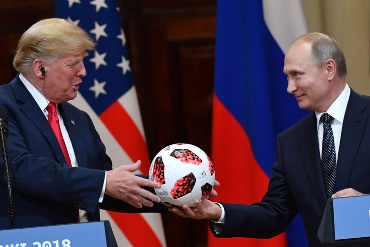 Russia's President Vladimir Putin offers a 2018 football World Cup ball to US President Donald Trump.