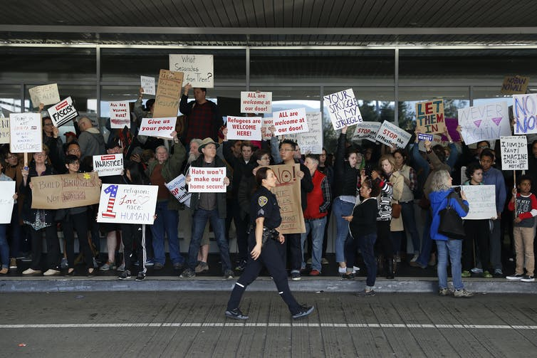 Protesters at the San Francisco airport hold signs reading 'refugees are welcome here' and 'build bridges not walls.'