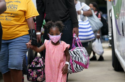 Families being evacuated by bus from Lake Charles, Louisiana, ahead of Hurricane Laura.