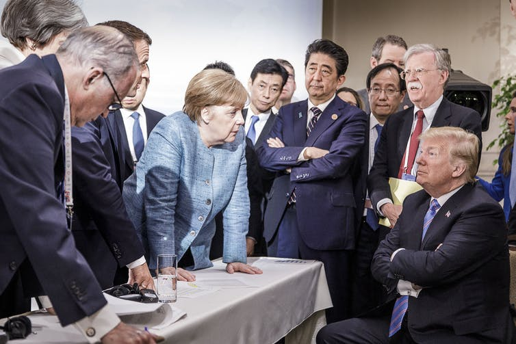 German Chancellor Angela Merkel and other leaders stare down at a seated Trump, who has his arms crossed