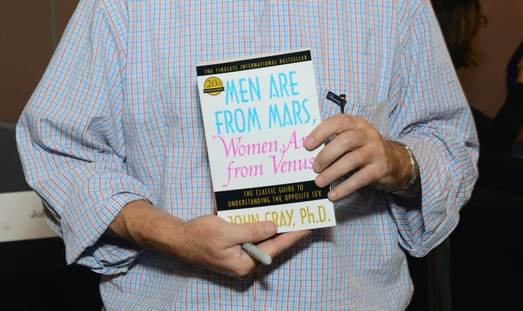A man holds a copy of 'Men Are from Mars, Women Are from Venus.'