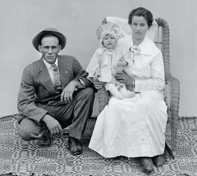 A stern-looking husband and wife pose with their child.