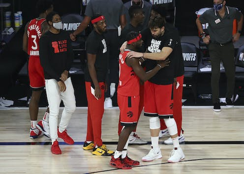 Toronto Raptors guard Terence Davis (0) reacts with center Marc Gasol (33) and other players convene at the side of the court.