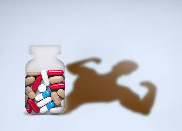 A bottle of pills casts a shadow in the shape of a body builder's torso flexing its biceps.