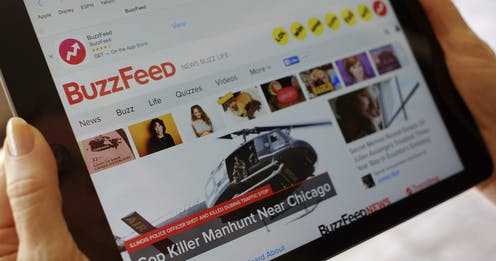 A woman holds a tablet with the Buzzfeed home page displayed.