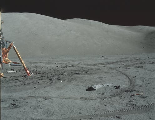 A golden lunar lander and tyre tracks on the Moon.
