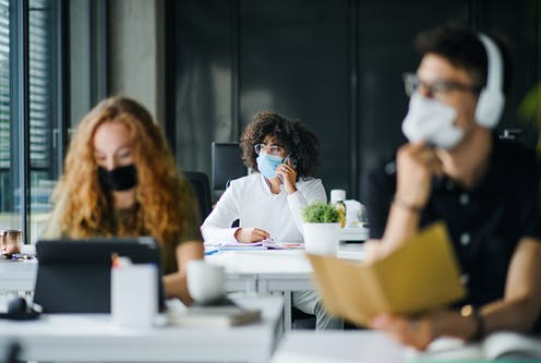 Three young adults wearing masks in office environment.