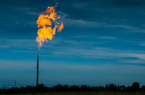 Gas burning from a tall factory pipe on a dark and dusky day.