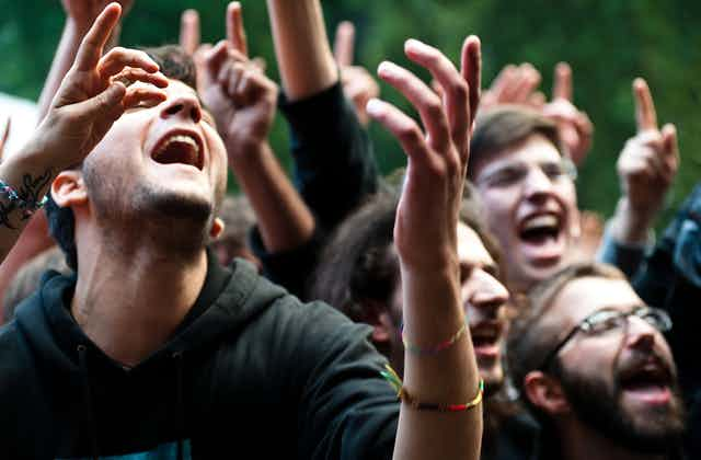 Young people in a crowd lifting their hands up as they sing