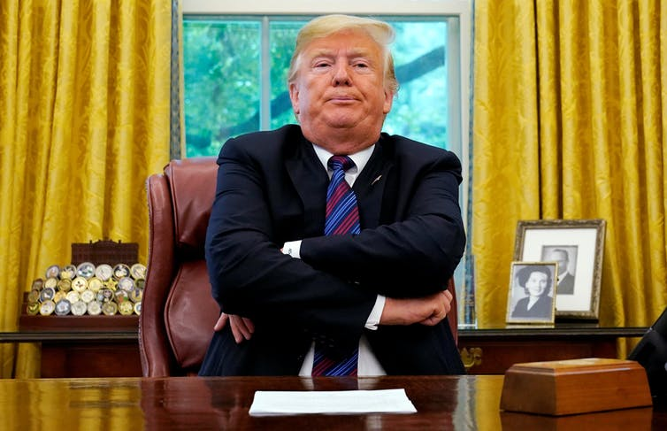 US President Donald Trump sitting at desk in White House